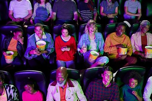 High angle view of audience enjoying comedy movie at cinema hall