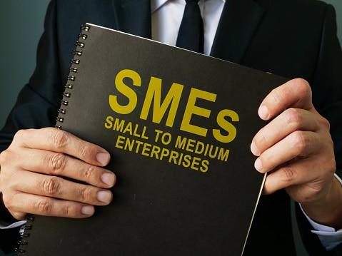 Businessman holds SMEs Small to Medium Enterprises.