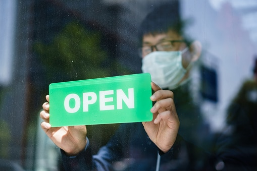 Happy business owner hanging an open sign while wearing protective mask