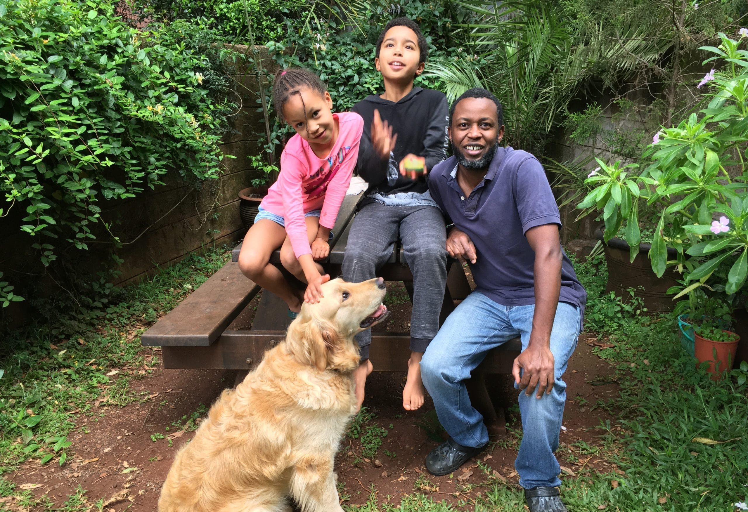 Kamweti wa Mutu with his two children; Charlie, 11, and Adia, 8, with their Golden Retriever, Nalia, pictured at their home in Nairobi