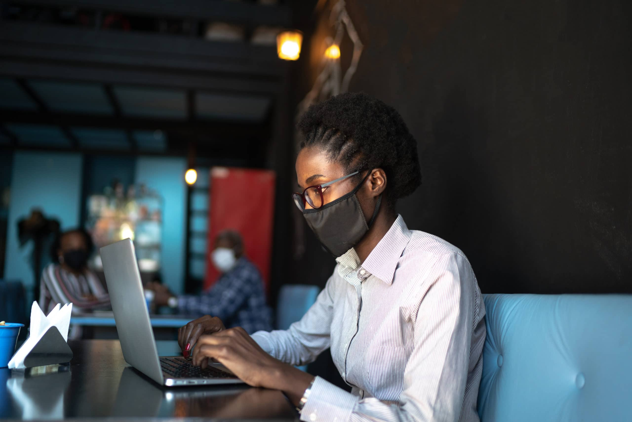 Young woman wearing a protective face mask and using a laptop in a restaurant