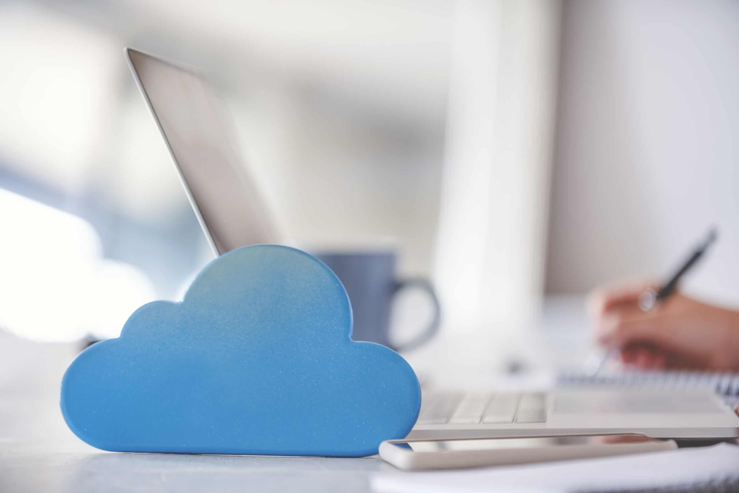 Woman using a laptop with cloud icon on working at home.