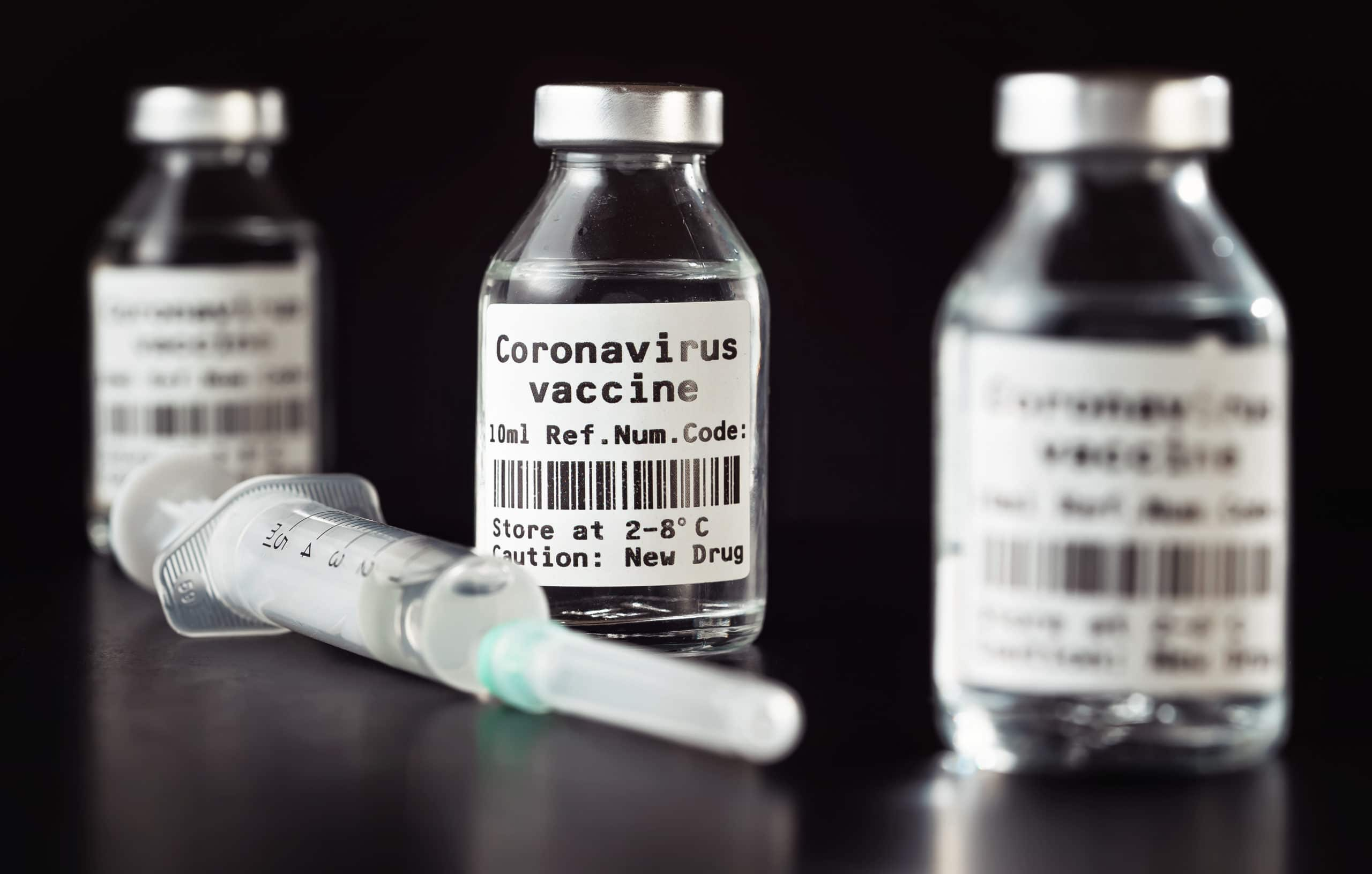 Coronavirus Covid-19 vaccine concept –  three glass vials on black table, hypodermic syringe needle near, closeup detail (label own design – dummy data and barcode, not real product)