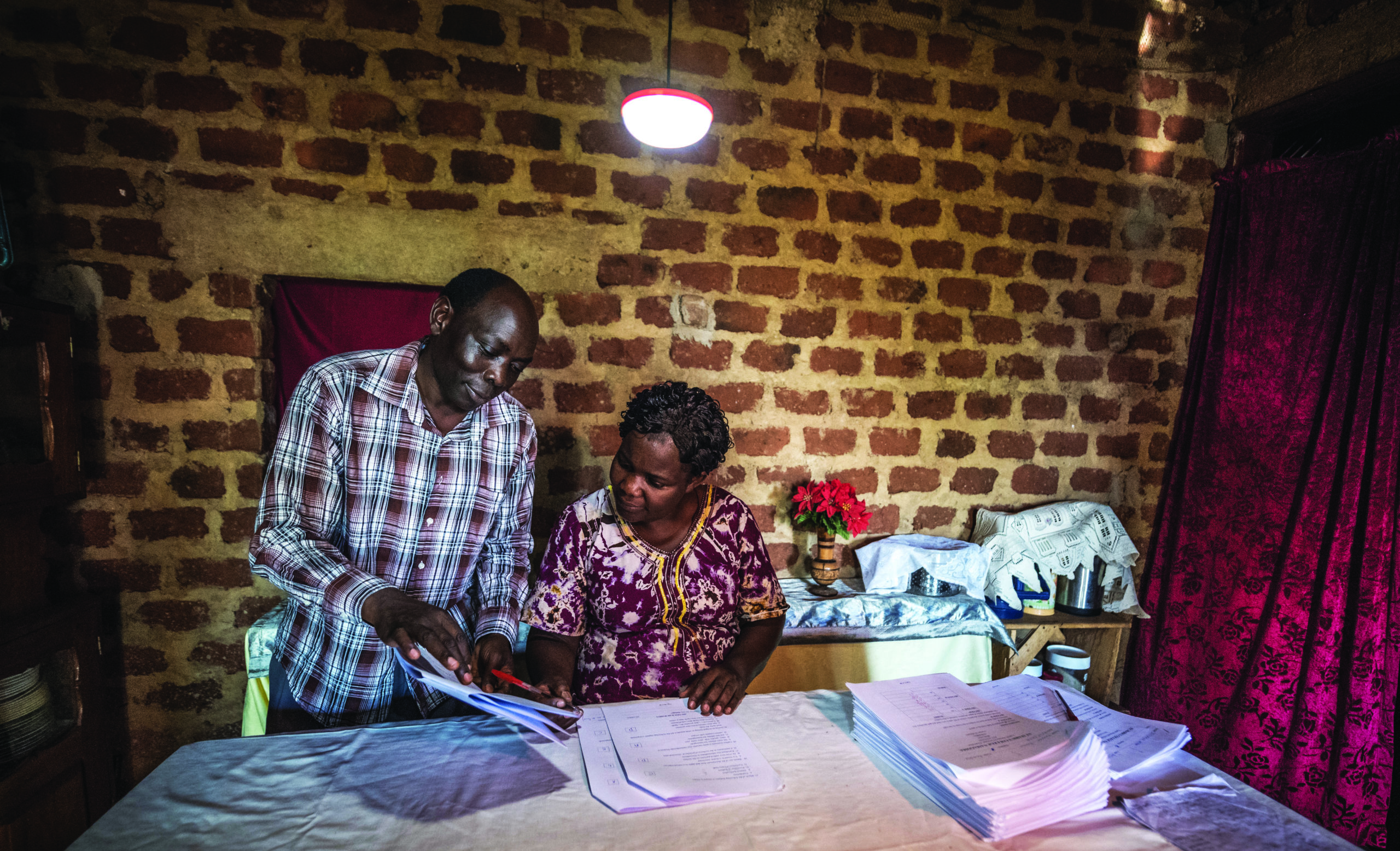 A rural classroom uses a solar powered light, a key product of East Africa's off-grid energy sector; image by FINCA International [A. Wright]