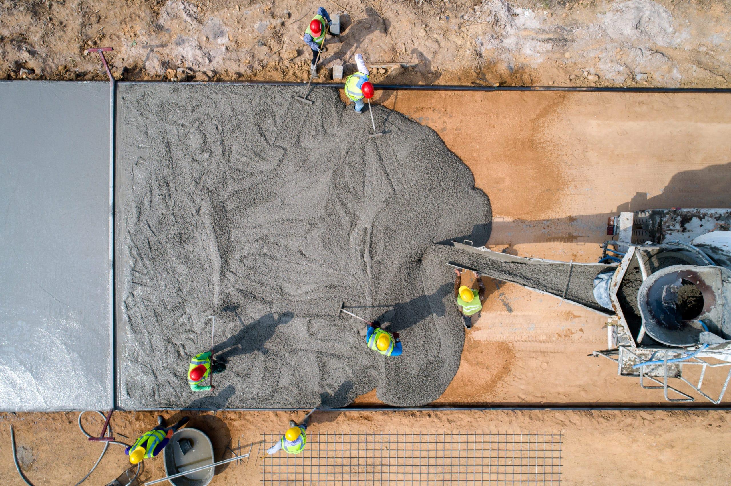 A construction worker pouring a wet concret at road construction site