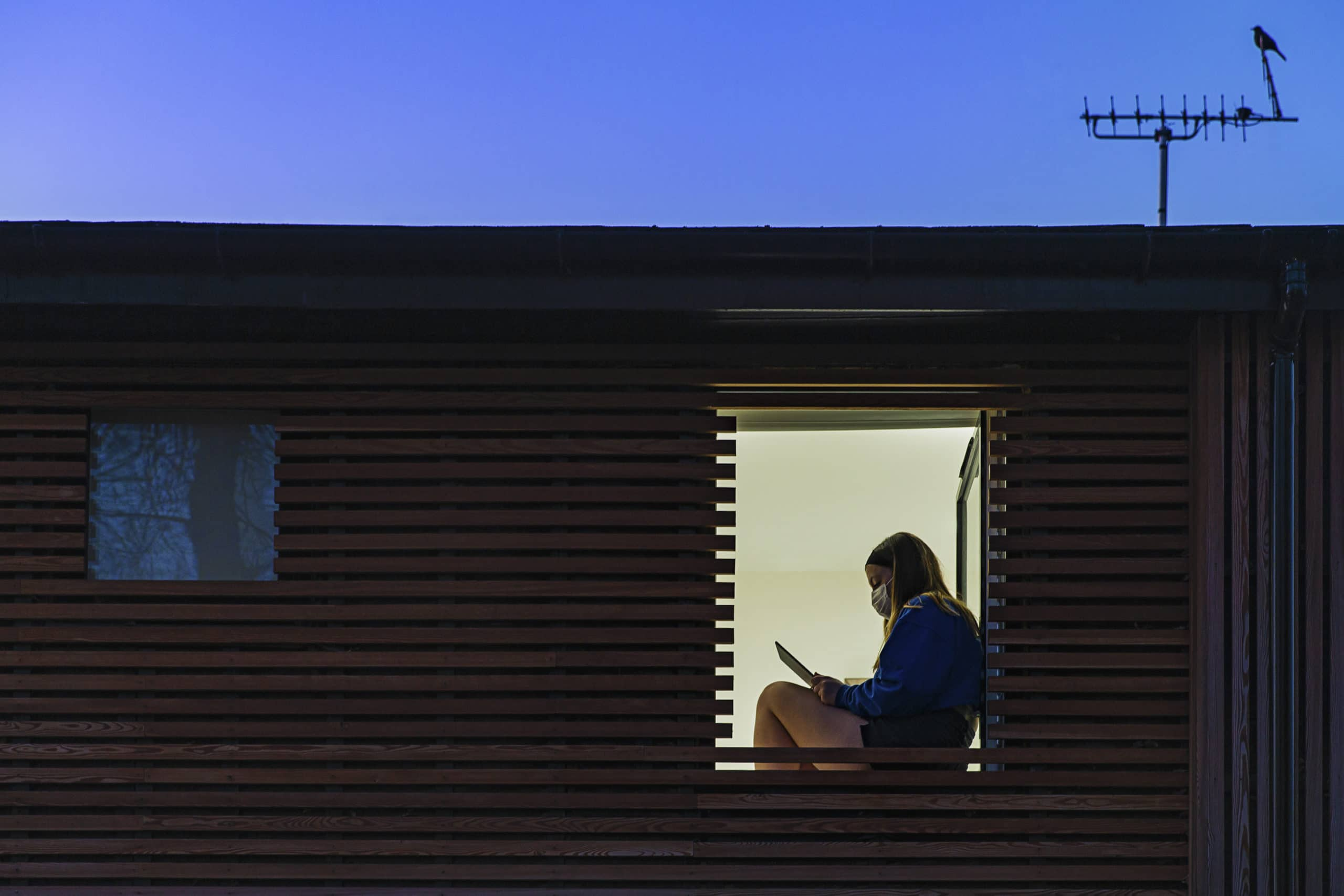 Teenage girl wearing mask sitting in her window