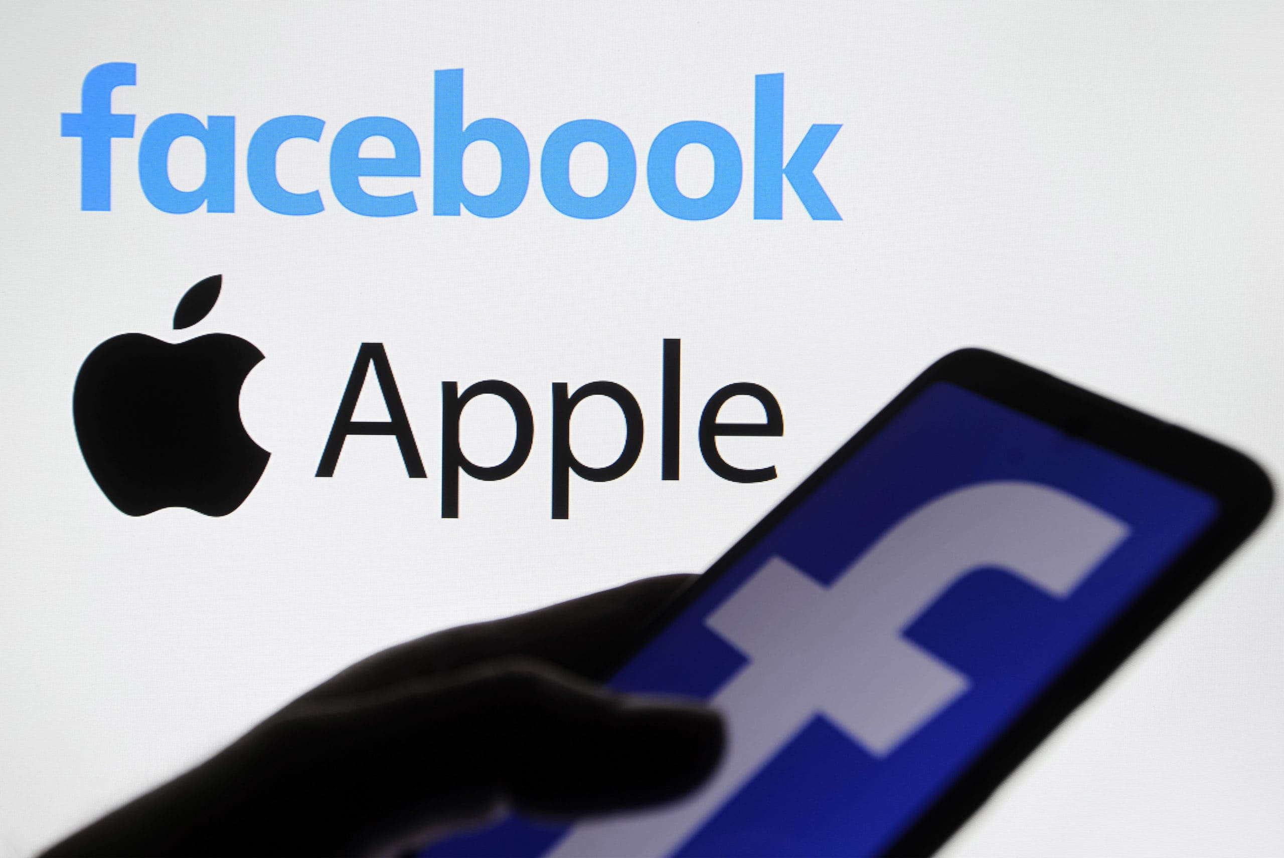 In this photo illustration the Apple and Facebook logos are