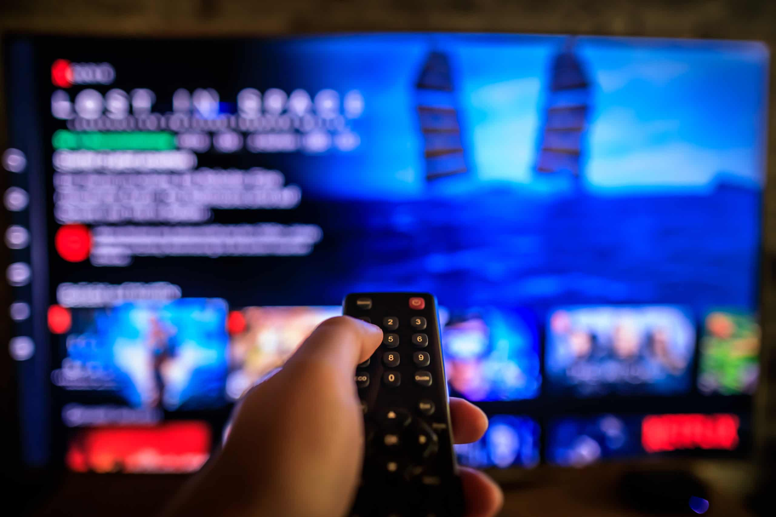 TV remote control in the foreground, Video on demand screen in the blurry background