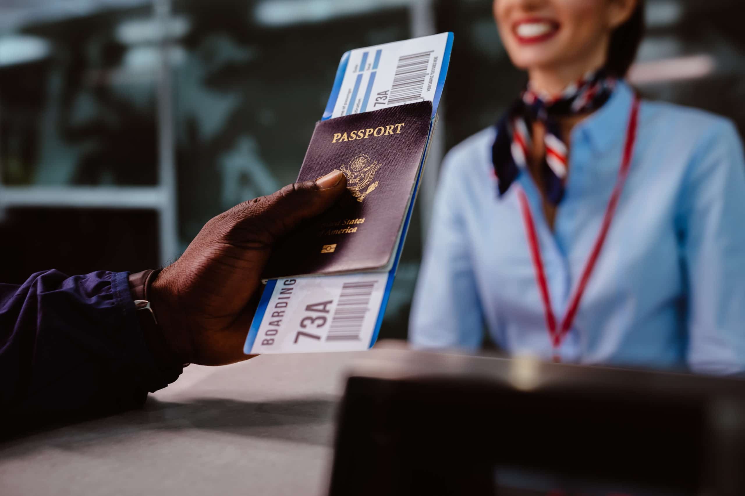 Man holding passport and boarding pass at airline check-in counter