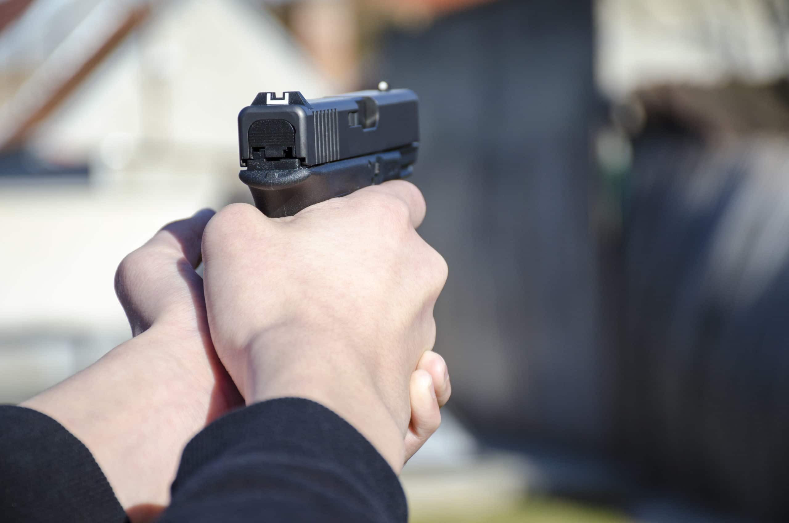 A gun in the hands of a man ready for a shot with blurred backfround.