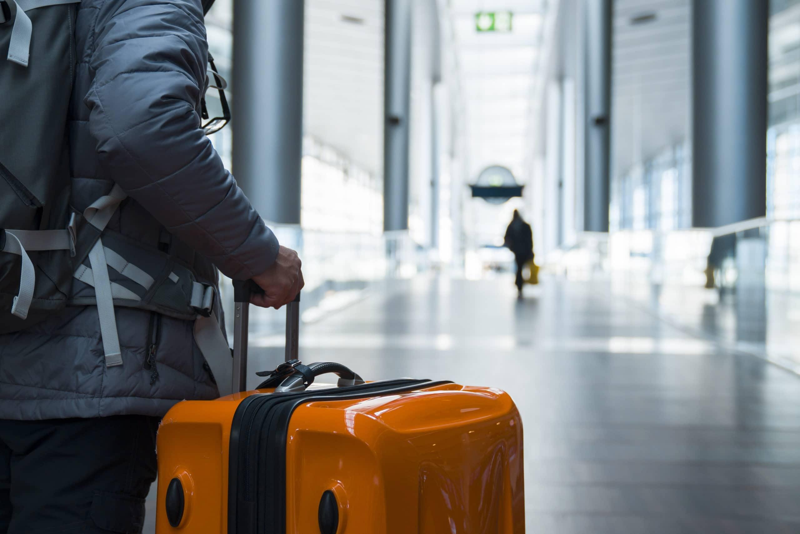 Man walking with suitcase at airport terminal
