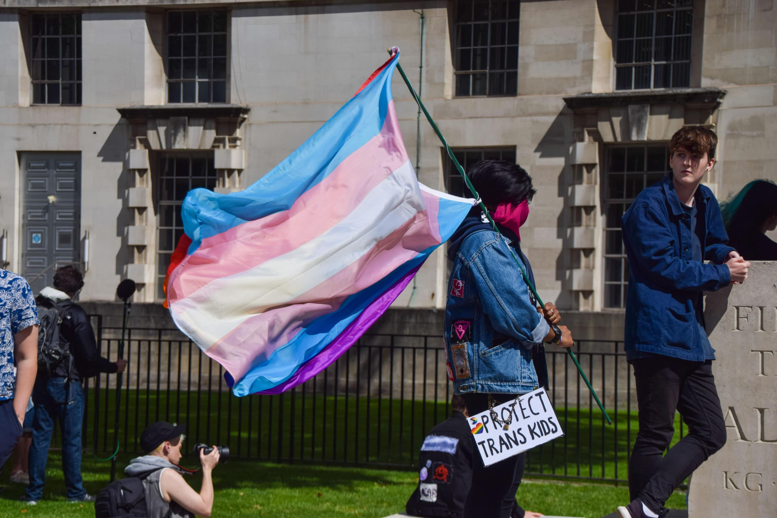A protester holds a Trans Pride flag and a 'Protect Trans