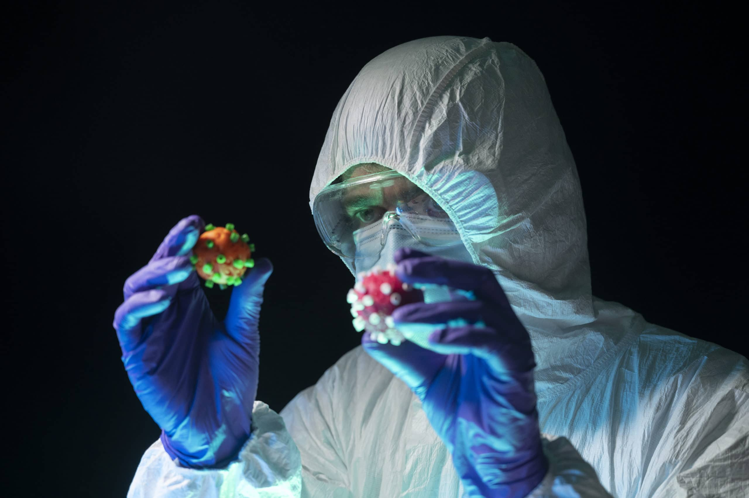 Scientist in a protective suit holds and compares two different Coronavirus of different color in his hands. Creative image.